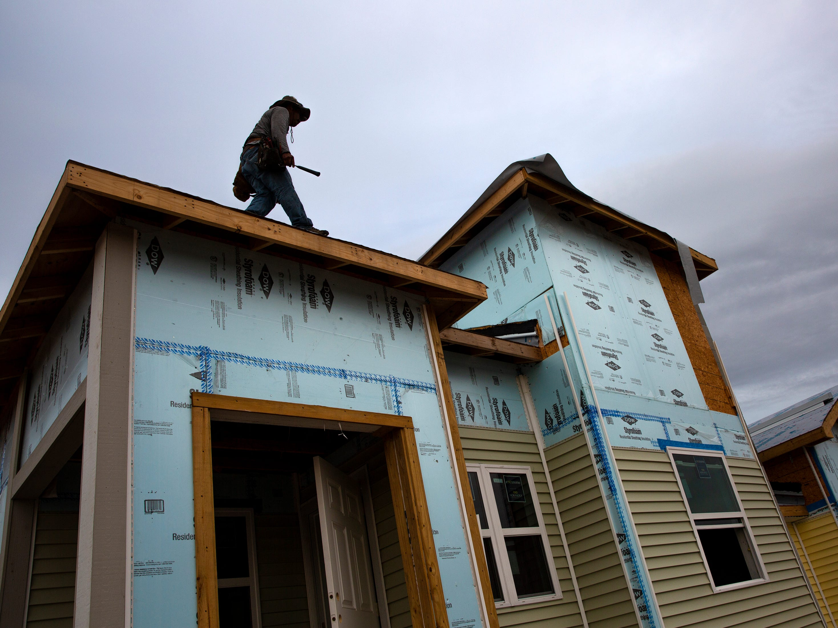 A contract worker with Habitat for Humanity of Collier County works on the roof of a home Saturday, Jan. 5, 2019, in the Dockside neighborhood in East Naples.
