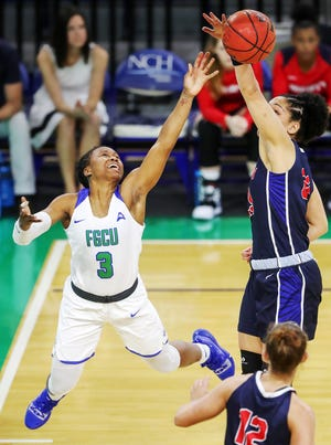 FGCU's Keri Jewett-Giles, left, drives to the basket against Liberty's Emily Lytle on Saturday at Alico Arena in Fort Myers.