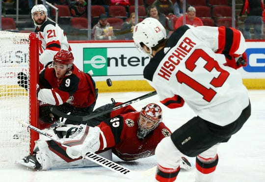 New Jersey Devils center Nico Hischier (13) scores a goal as he gets the puck past Arizona Coyotes goaltender Darcy Kuemper (35) and center Clayton Keller (9) as Devils right wing Kyle Palmieri (21) watches during the first period of an NHL hockey game Friday, Jan. 4, 2019, in Glendale, Ariz. The puck did not actually go into the net but it was ruled a goal due to Coyotes center Clayton Keller moving the net out of place and the puck would have gone in for the score.
