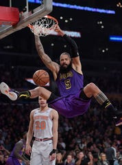 Los Angeles Lakers center Tyson Chandler, top, dunks as New York Knicks forward Kevin Knox watches during the first half of an NBA basketball game Friday, Jan. 4, 2019, in Los Angeles.
