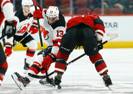 New Jersey Devils center Nico Hischier (13) gets tripped up by Arizona Coyotes center Brad Richardson, right, during the first period of an NHL hockey game Friday, Jan. 4, 2019, in Glendale, Ariz.