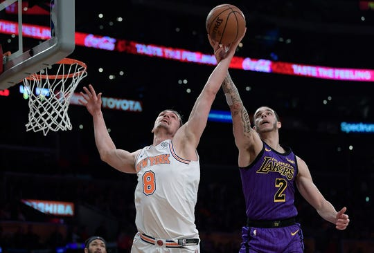 New York Knicks forward Mario Hezonja, left, and Los Angeles Lakers guard Lonzo Ball reach for a rebound during the second half of an NBA basketball game Friday, Jan. 4, 2019, in Los Angeles. The Knicks won 119-112.