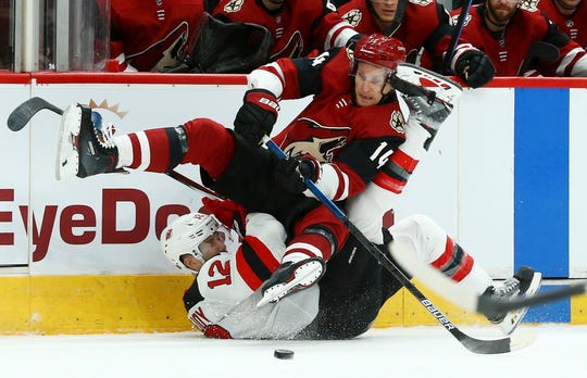 Arizona Coyotes right wing Richard Panik (14) flips over New Jersey Devils defenseman Ben Lovejoy (12) as Panik passes the puck during the first period of an NHL hockey game Friday, Jan. 4, 2019, in Glendale, Ariz.
