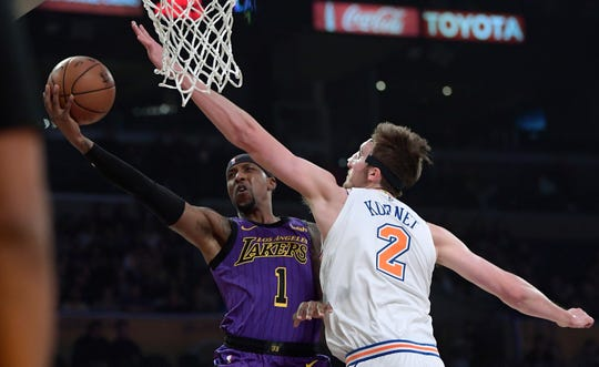Los Angeles Lakers guard Kentavious Caldwell-Pope, left, shoots as New York Knicks forward Luke Kornet defends during the first half of an NBA basketball game Friday, Jan. 4, 2019, in Los Angeles.