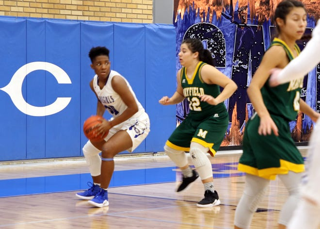 Dayshaun Moore pulls down a rebound while Alize Ruiz looks to steal the ball.