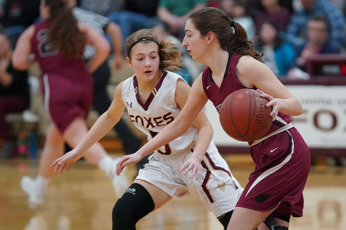 Taylor Hammonds (4) of Mayville moves the ball past Hannah Fedderly (5) of Omro. The Omro Foxes hosted the Mayville Cardinals in a Flyway Conference basketball game Friday evening, January 4, 2019.