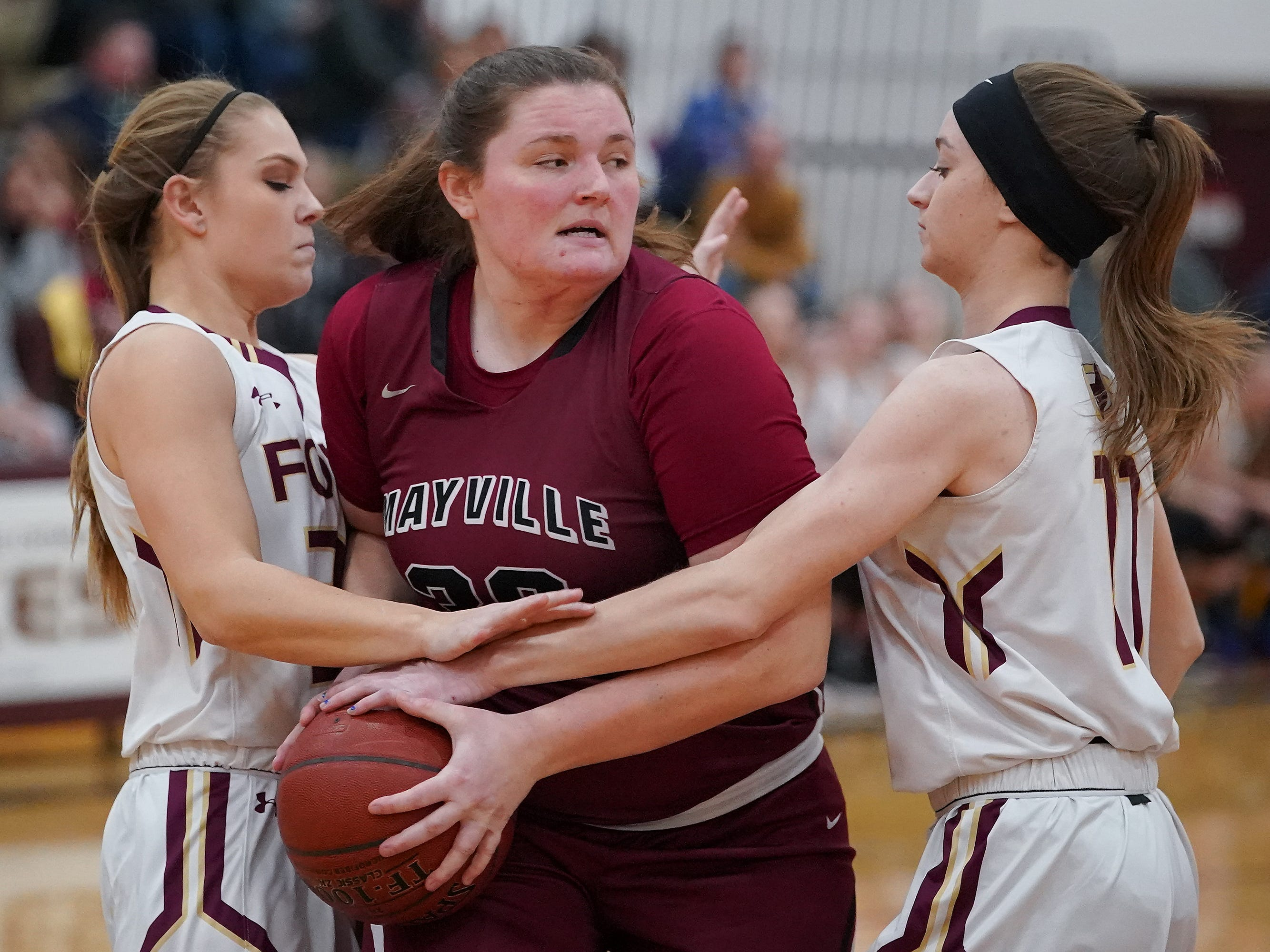Sydney Schultz (30) of Mayville tries to battle her way past Danycka Milis (11) and Jadeyn Yonke (22) of Omro. The Omro Foxes hosted the Mayville Cardinals in a Flyway Conference basketball game Friday evening, January 4, 2019.