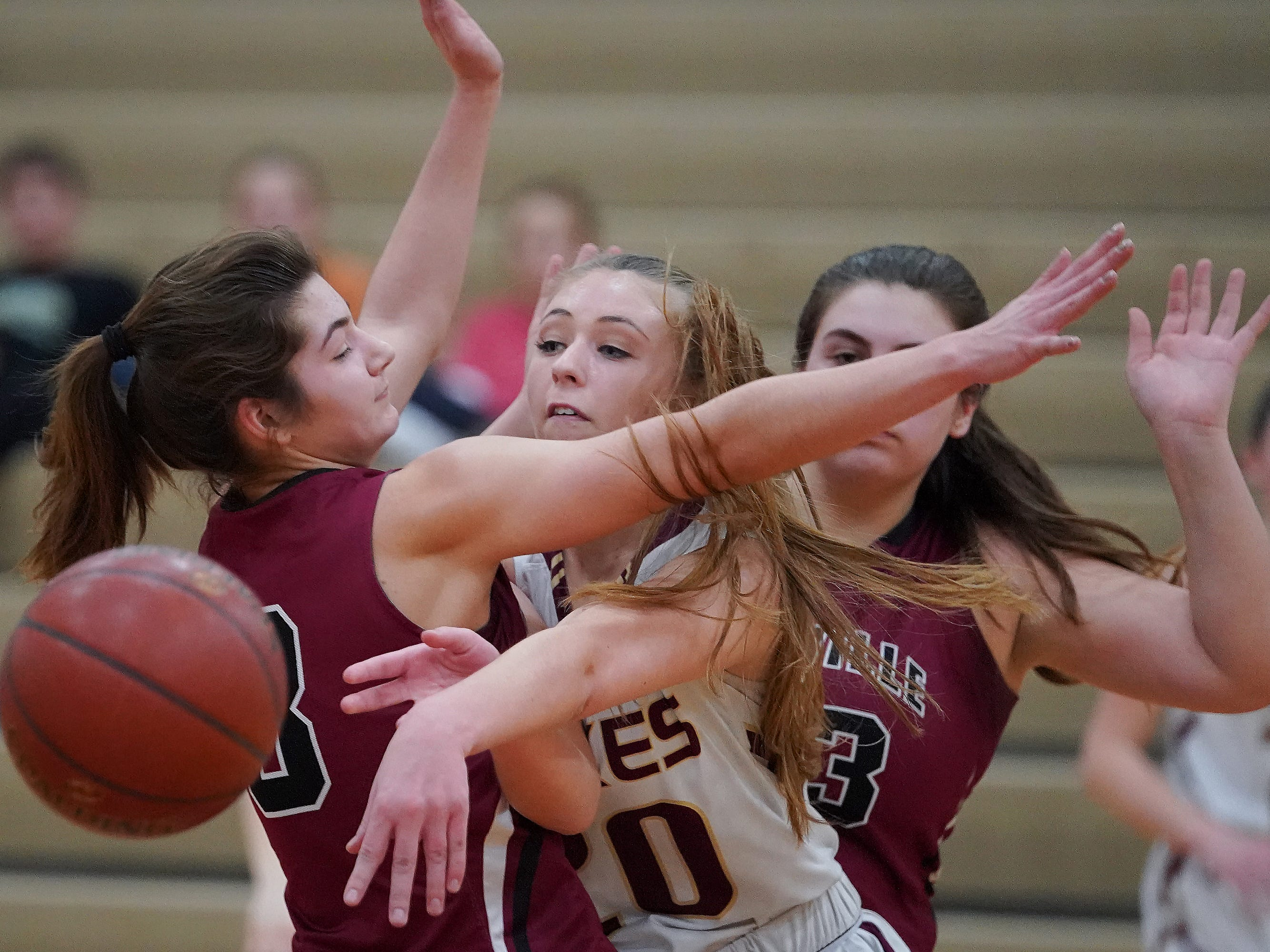 Taylor Lewis (20) of Omro manages to throw a pass while covered by Amber Schraufnagel (3) of Mayville. The Omro Foxes hosted the Mayville Cardinals in a Flyway Conference basketball game Friday evening, January 4, 2019.