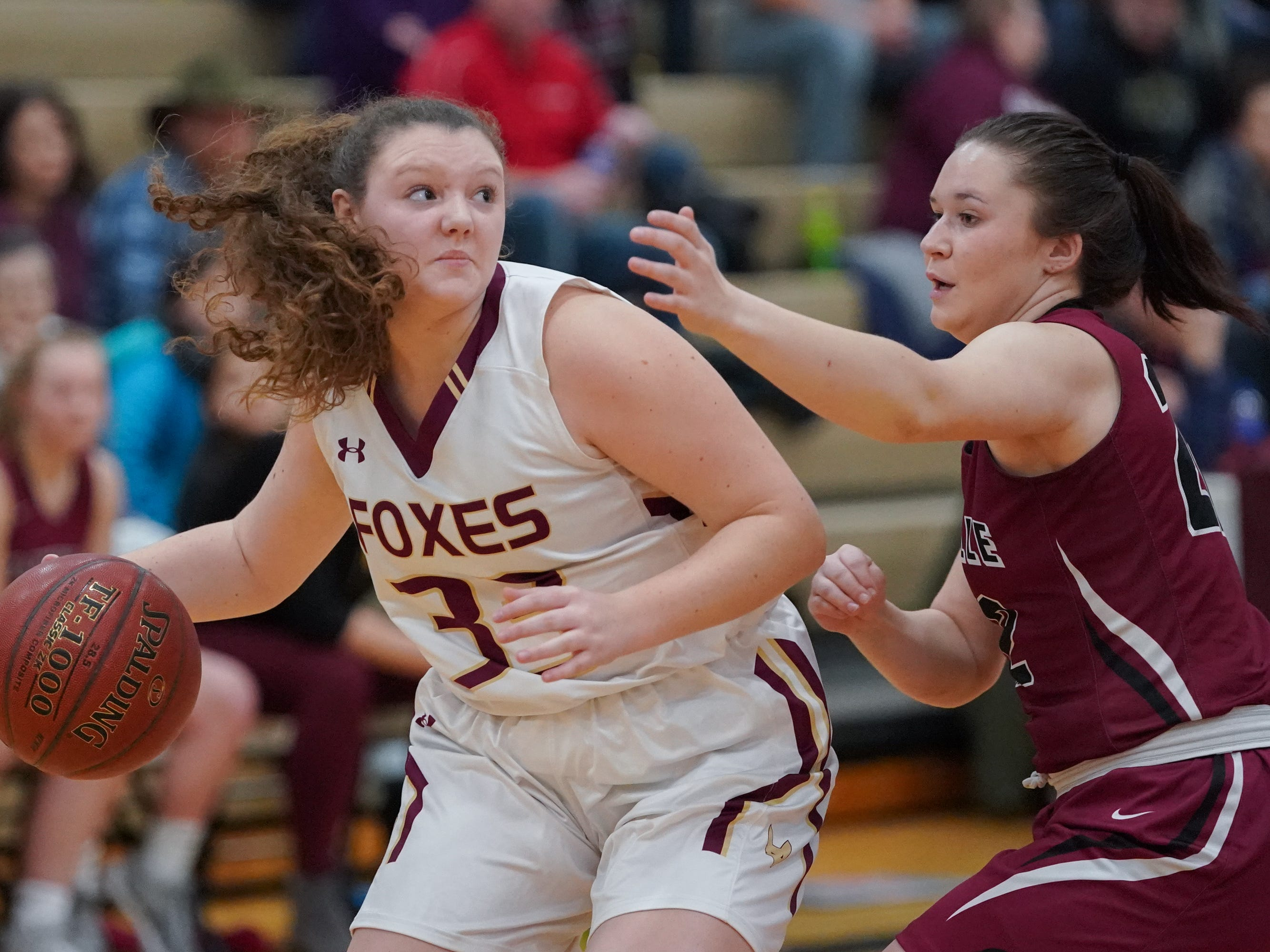Autumn Davis (33) of Omro drives around Reannah Zimmer (22) of Mayville. The Omro Foxes hosted the Mayville Cardinals in a Flyway Conference basketball game Friday evening, January 4, 2019.