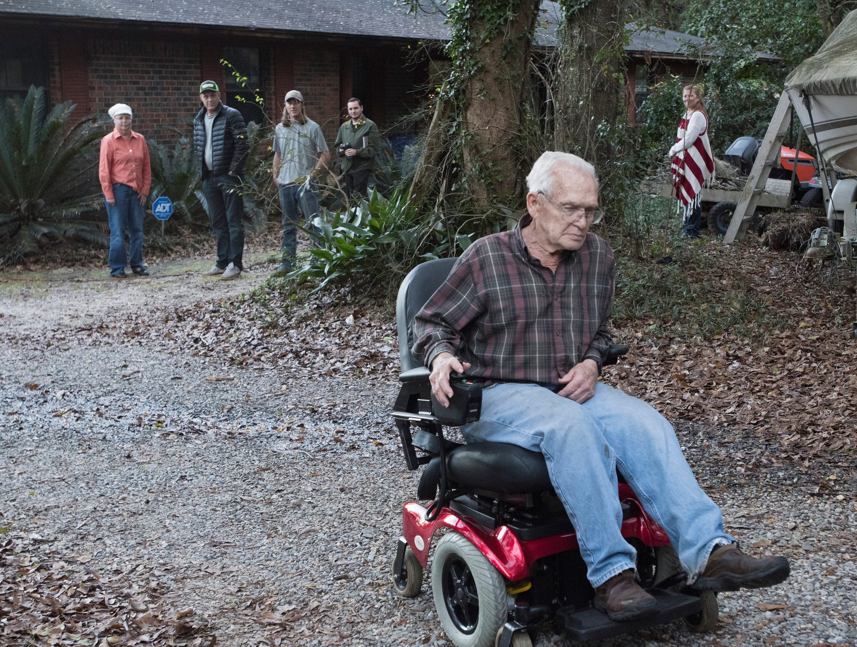 East Milton resident, Jim Blazier, takes his new motorized chair for a spin outside his home on Friday, Jan. 4, 2019, while his wife Phyllis, and Rick Beech, and others look on.  Blazier and his wife received the restored chair as a gift from Rick Beech, the owner of Beech Boys Lawn Care.