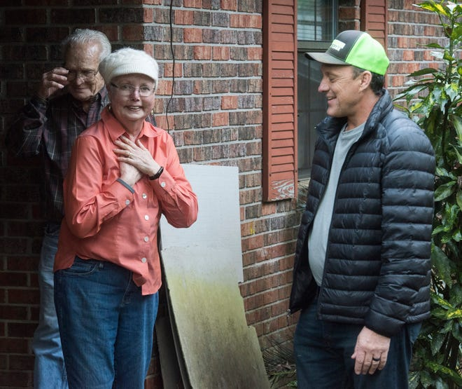 East Milton resident Phyllis and Jim Blazier are overcome with emotion Friday after a surprise delivery of a motorized wheelchair to their home as Rick Beech, the owner of Beech Boys Lawn Care, looks on.
