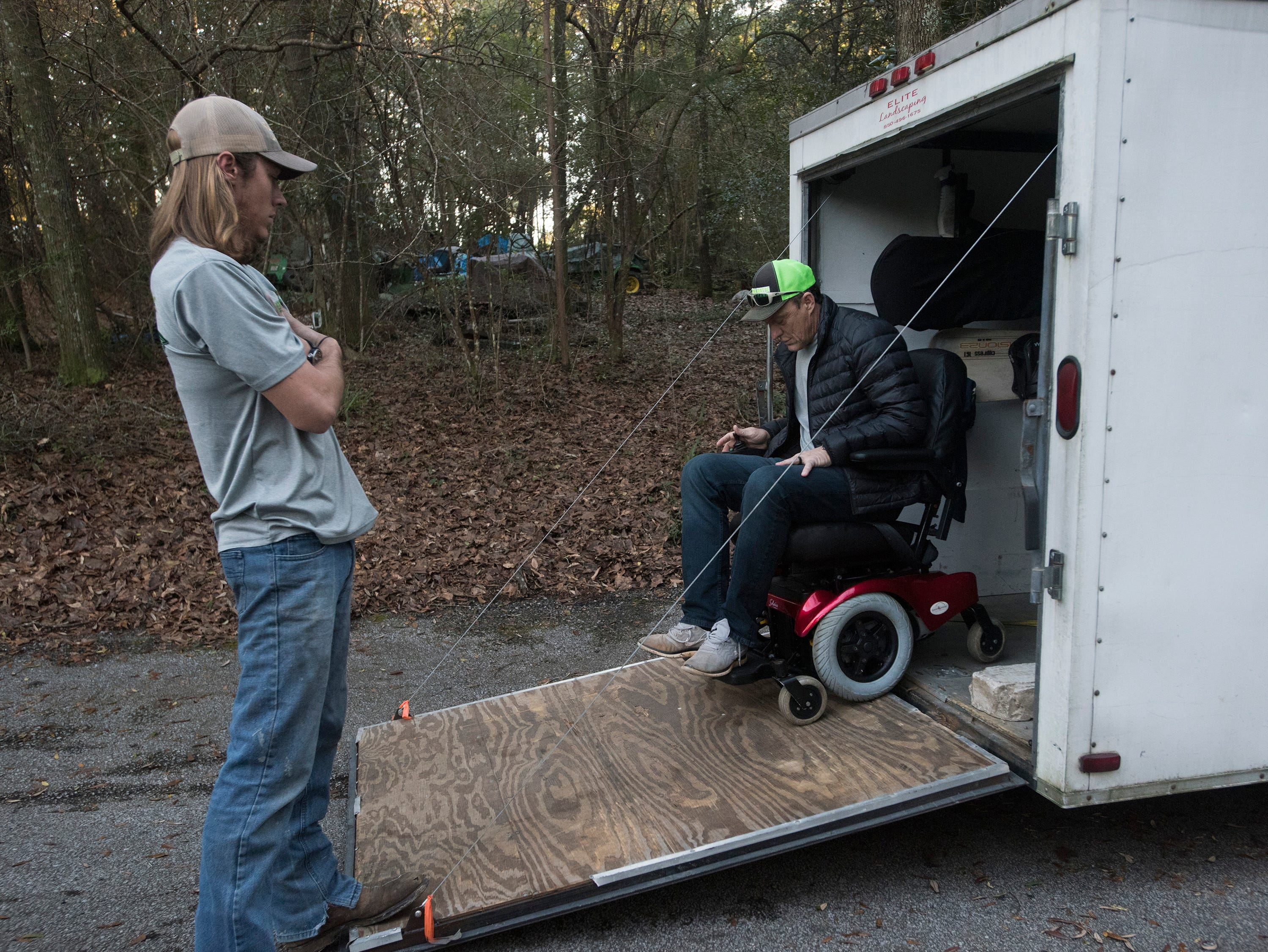 Rick Beech, the owner of Beech Boys Lawn Care, unloads a newly refurbished motorized chair outside the East Milton home of  Phyllis, and Jim Blazier, on Friday, Jan. 4, 2019, while his son, Cole looks on.