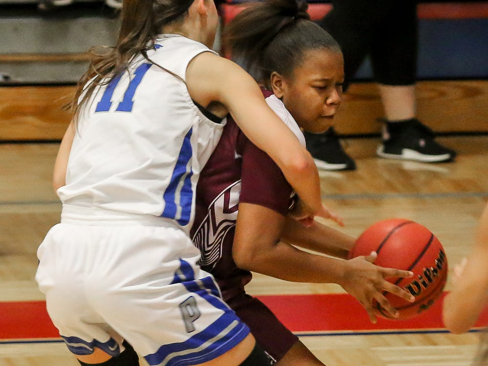 Pace's Katie Brabham (11) wraps up PHS' Joniya Perry (35) at Pace High School on Friday, January 4, 2019.
