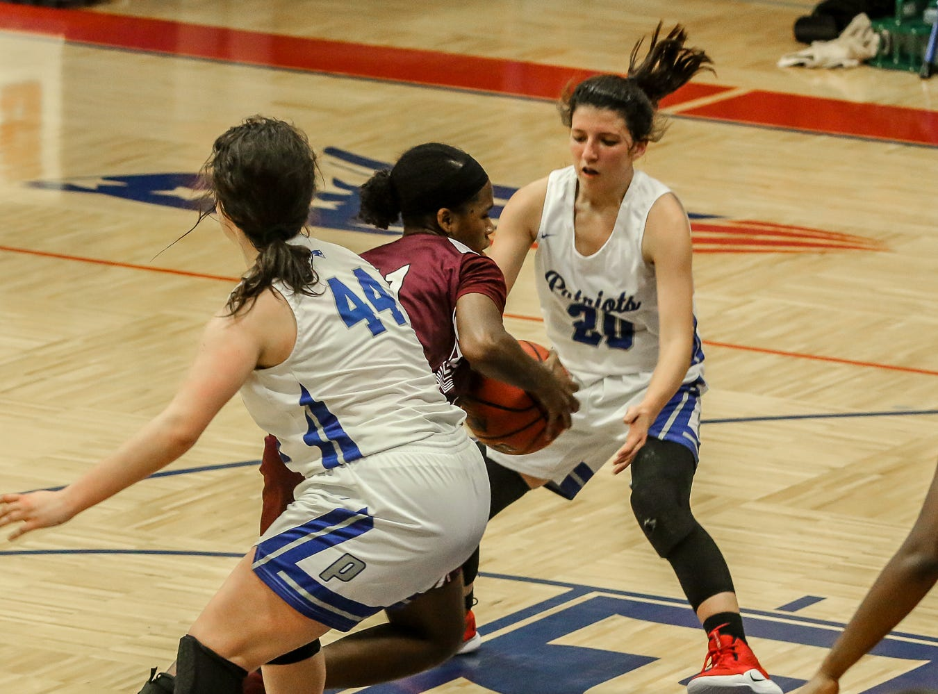 PHS' Nala Baker (11) drives in between Pace's Paiten Rivera (44) and Shay Crooks (20) at Pace High School on Friday, January 4, 2019.