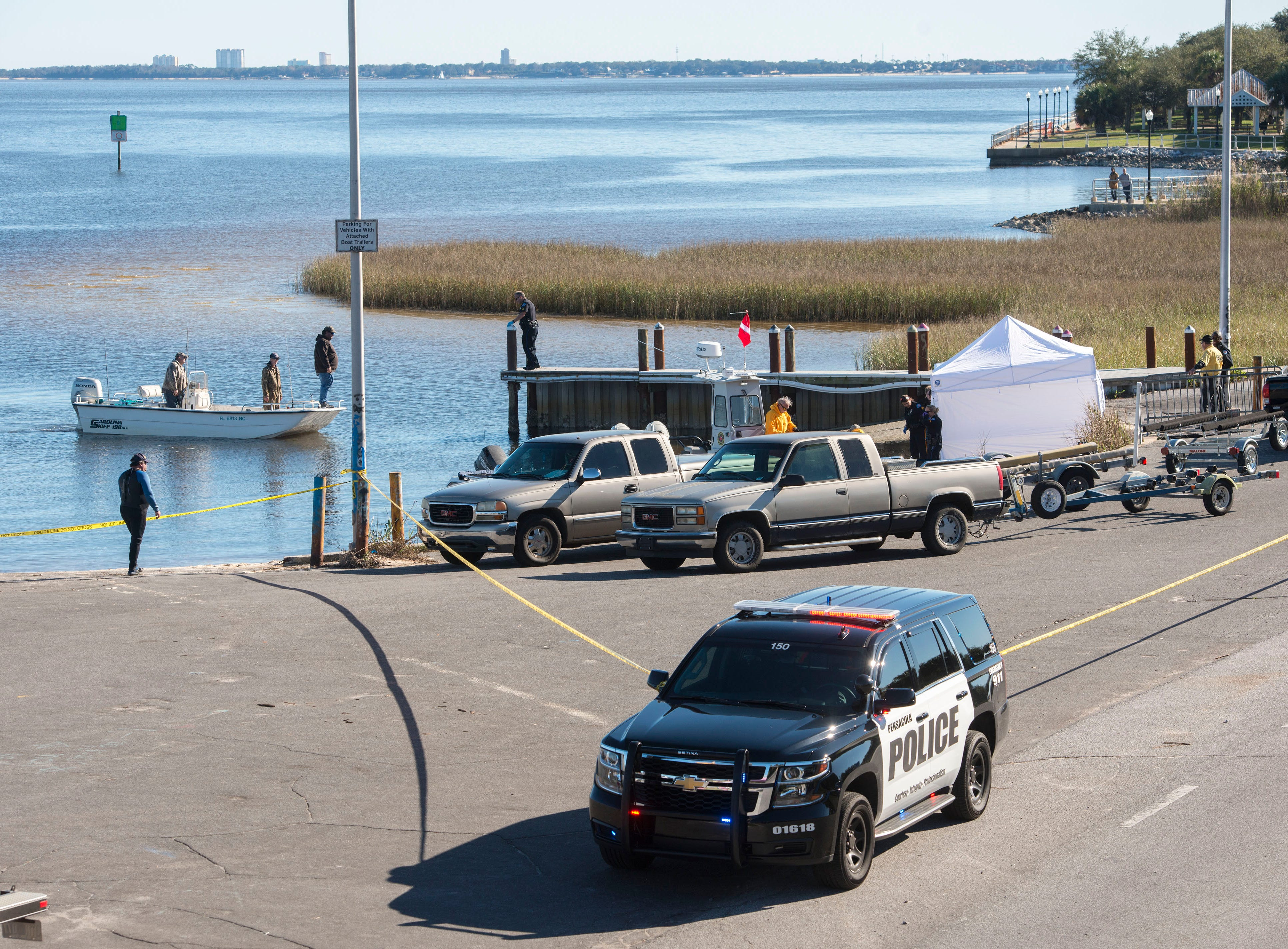 Pensacola police officers investigate a body found in Pensacola Bay Saturday, January 5, 2019 at the 17th Ave. boat ramp.