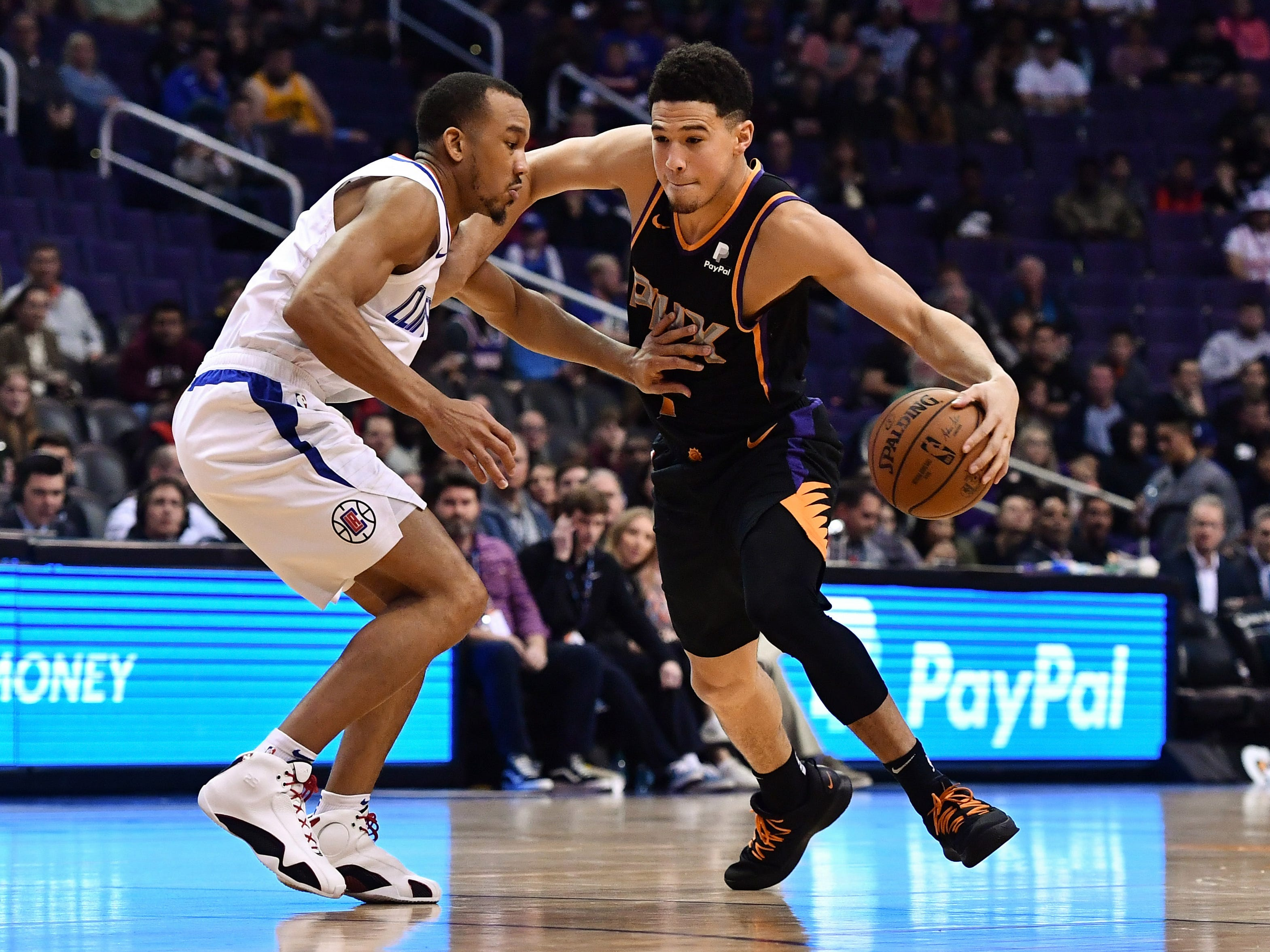 Jan 4, 2019; Phoenix, AZ, USA; Phoenix Suns guard Devin Booker (1) handles the ball against LA Clippers guard Avery Bradley (11) in the first half at Talking Stick Resort Arena. Mandatory Credit: Jennifer Stewart-USA TODAY Sports