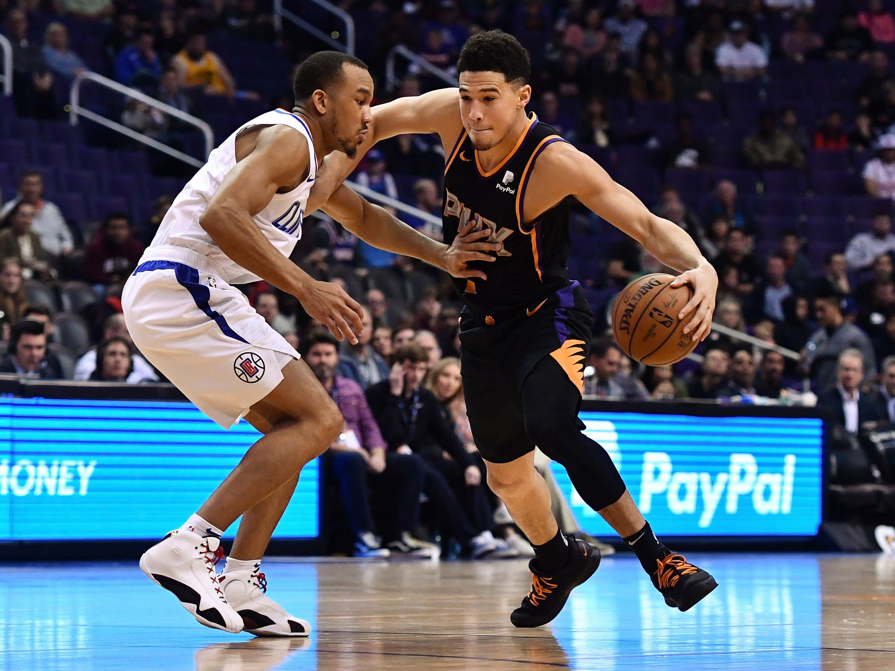 Jan 4, 2019; Phoenix, AZ, USA; Phoenix Suns guard Devin Booker (1) handles the ball against LA Clippers guard Avery Bradley (11) in the first half at Talking Stick Resort Arena. Mandatory Credit: Jennifer Stewart-USA TODAY Sports