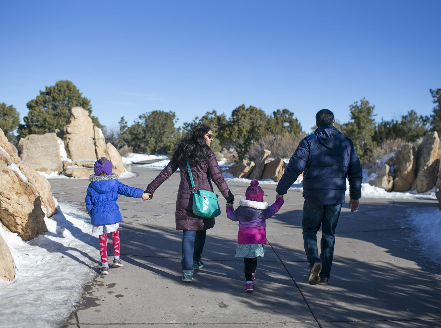 Neha Sharma (center left) holds hands with her daughters, 5-year-old Navya Sharma (left) and 2-year-old Avanya Sharma (center right), as they walk with their father, Vivek Rohilla (right), at Grand Canyon National Park while visiting from Seattle on Jan. 4, 2019. The park was staffed at minimum capacity due to the government shutdown but retained much of its services due to an executive order issued by Arizona Gov. Doug Ducey to run the park with state funds in the event of a shutdown.