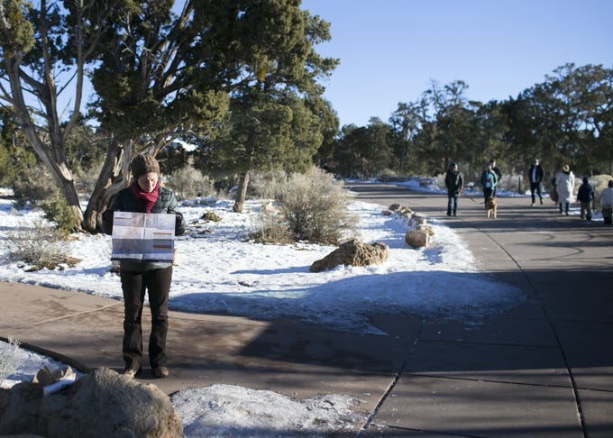 SooHyun Tak (left), visiting from Washington, D.C., looks at a map near the closed visitor center at Grand Canyon National Park on Jan. 4, 2019. The park was staffed at minimum capacity due to the government shutdown but retained much of its services due to an executive order issued by Arizona Gov. Doug Ducey to run the park with state funds in the event of a shutdown.