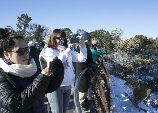 Visitors look out over the edge at Grand Canyon National Park on Jan. 4, 2019. The park was staffed at minimum capacity due to the government shutdown but retained much of its services due to an executive order issued by Arizona Gov. Doug Ducey to run the park with state funds in the event of a shutdown.