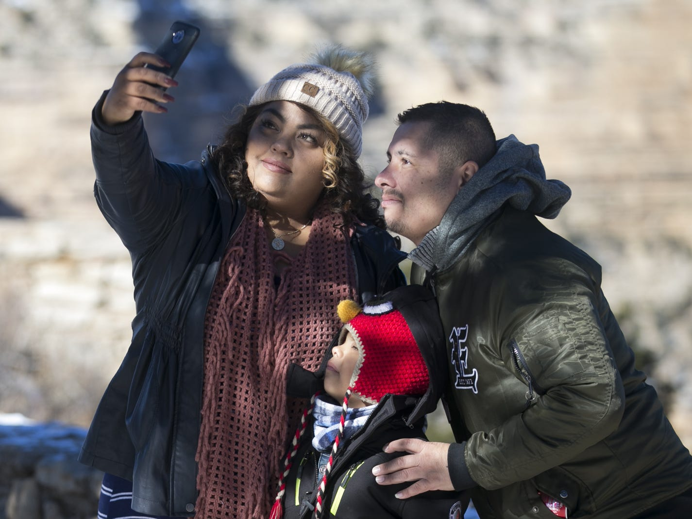 Angie Sosa (left) poses for a photo with Christian Alvarez (right) and 6-year-old Xavier Rodriquez-Alvarez (center) at Grand Canyon National Park on Jan. 4, 2019. The park was staffed at minimum capacity due to the government shutdown but retained much of its services due to an executive order issued by Arizona Gov. Doug Ducey to run the park with state funds in the event of a shutdown.