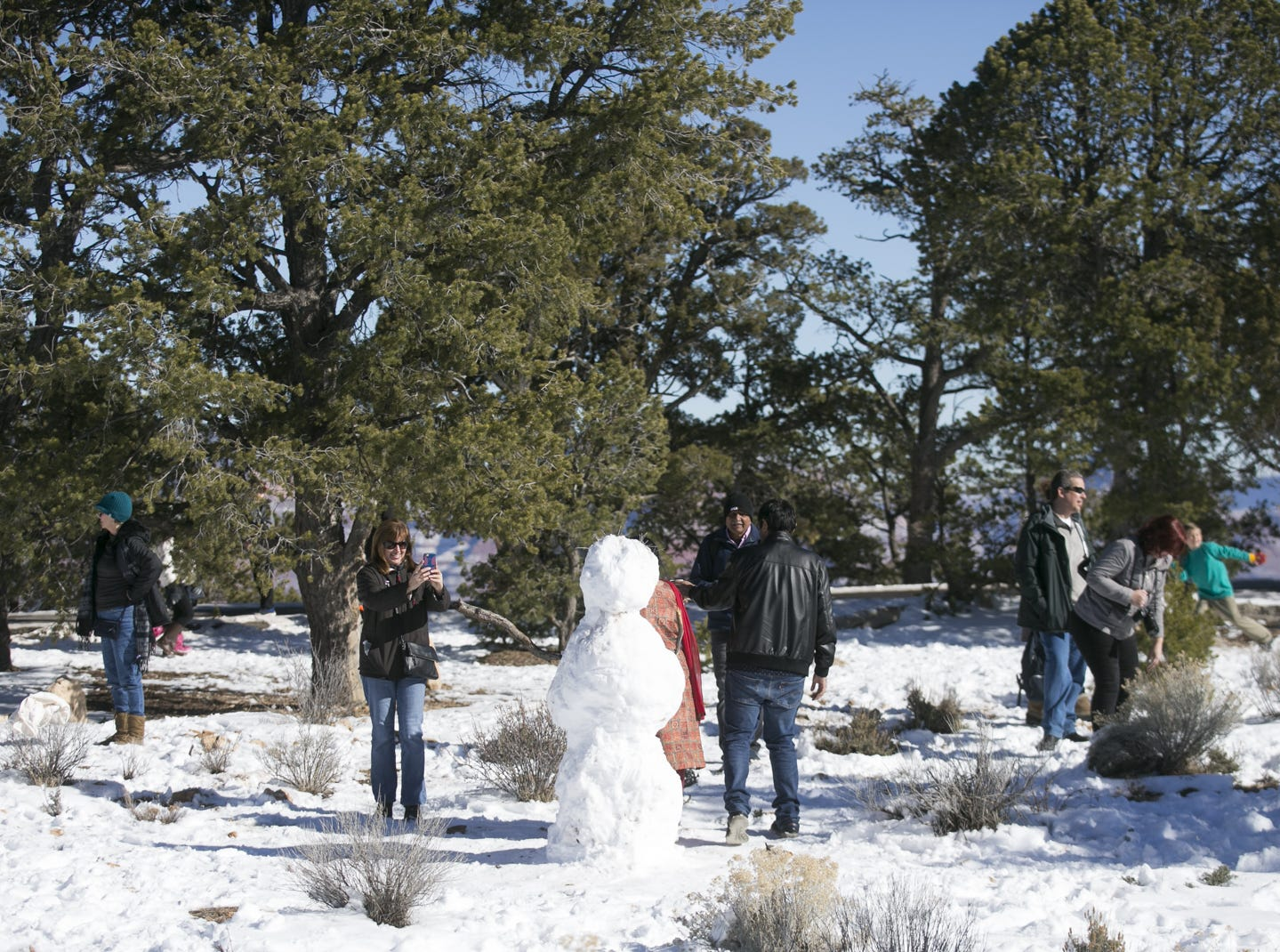 Visitors make a snowman near the rim of Grand Canyon National Park on Jan. 4, 2019. The park was staffed at minimum capacity due to the government shutdown but retained much of its services due to an executive order issued by Arizona Gov. Doug Ducey to run the park with state funds in the event of a shutdown.