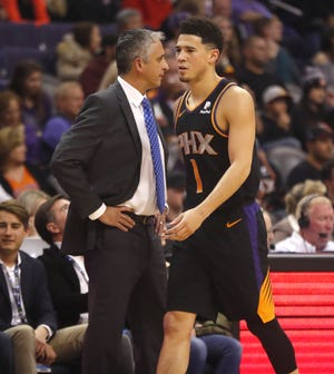 Suns' Devin Booker (1) walks off the court past head coach Igor Kokoskov during the first half against the Clippers at Talking Stick Resort Arena in Phoenix, Ariz. on January 4, 2019.