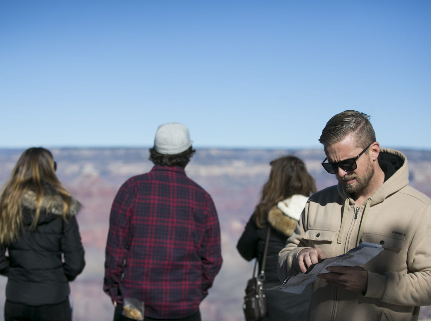 Collin Murphy (right) from Orange County, California, looks at a map of Grand Canyon National Park on Jan. 4, 2019. The park was staffed at minimum capacity due to the government shutdown but retained much of its services due to an executive order issued by Arizona Gov. Doug Ducey to run the park with state funds in the event of a shutdown.