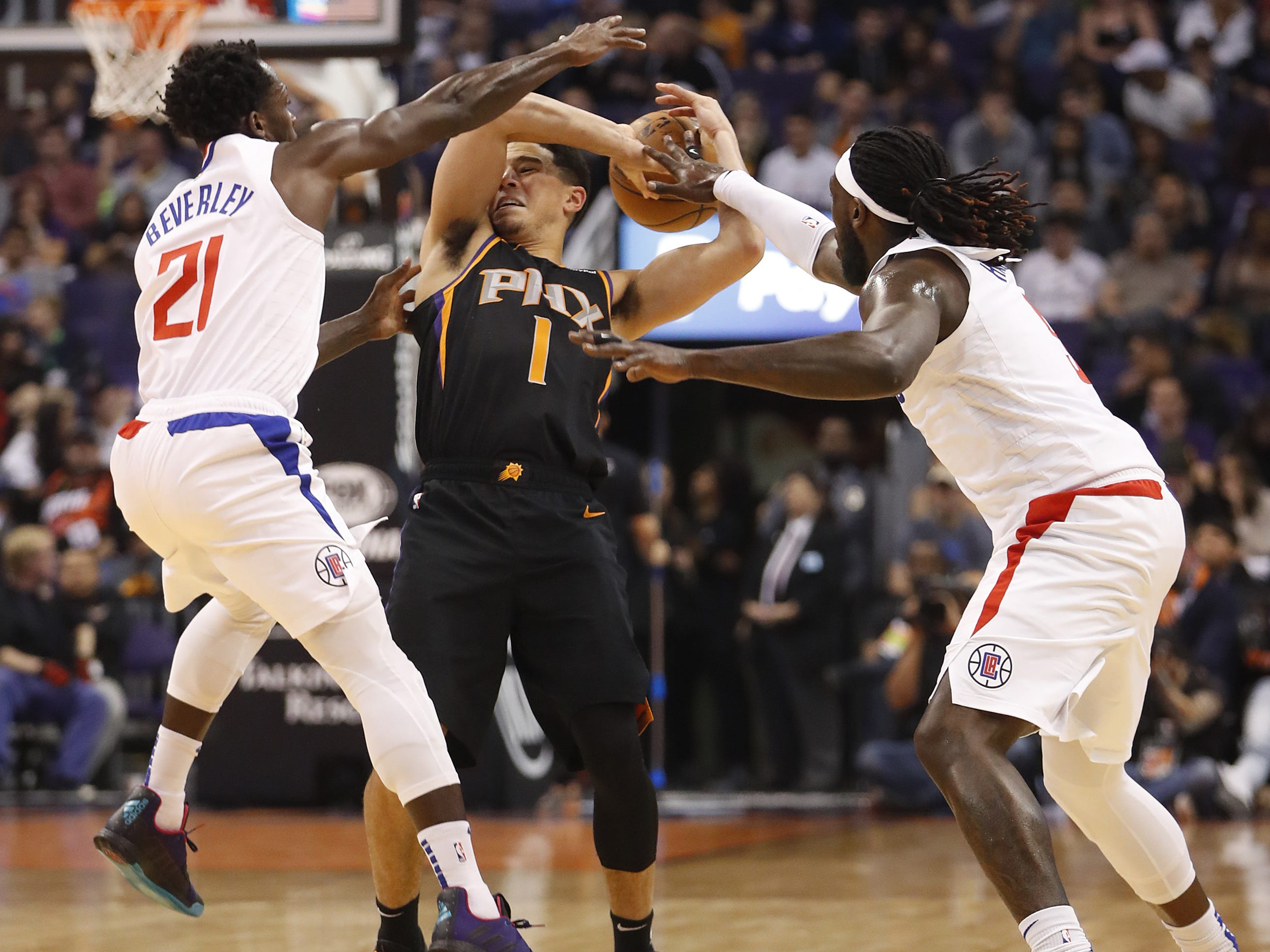 Clippers' Patrick Beverley (21) and Montrezl Harrell (5) force a steal on Suns' Devin Booker (1) during the first half at Talking Stick Resort Arena in Phoenix, Ariz. on January 4, 2019.