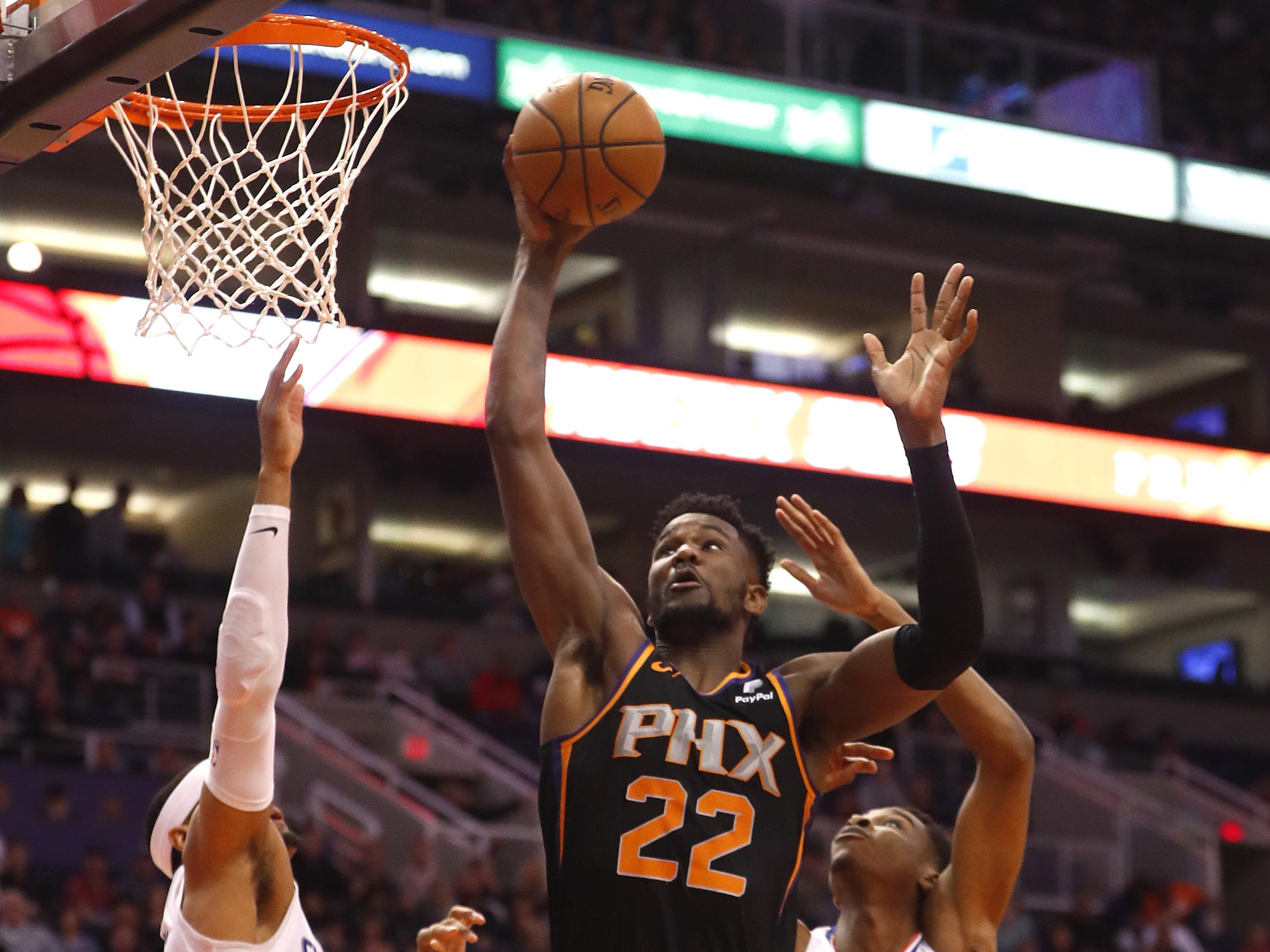 Suns' Deandre Ayton (22) grabs a pass against Clippers' Tobias Harris (34) and Shai Gilgeous-Alexander (2) during the first half at Talking Stick Resort Arena in Phoenix, Ariz. on January 4, 2019.