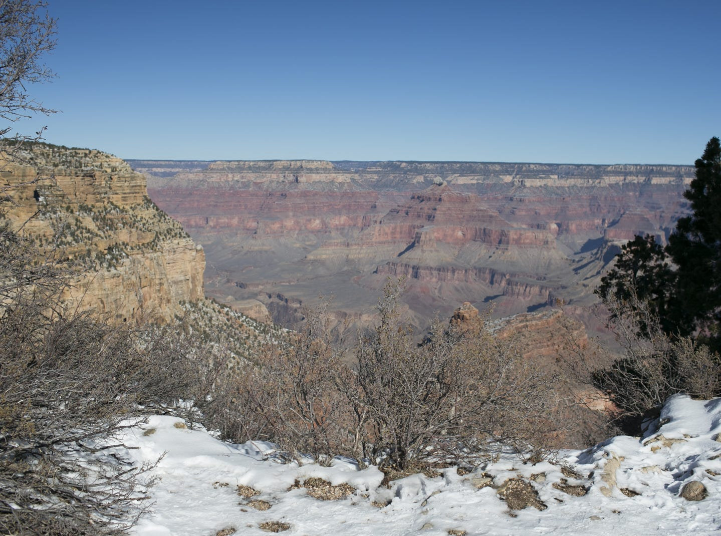 Snow rests near a path at Grand Canyon National Park on Jan. 4, 2019. The park was staffed at minimum capacity due to the government shutdown but retained much of its services due to an executive order issued by Arizona Gov. Doug Ducey to run the park with state funds in the event of a shutdown.
