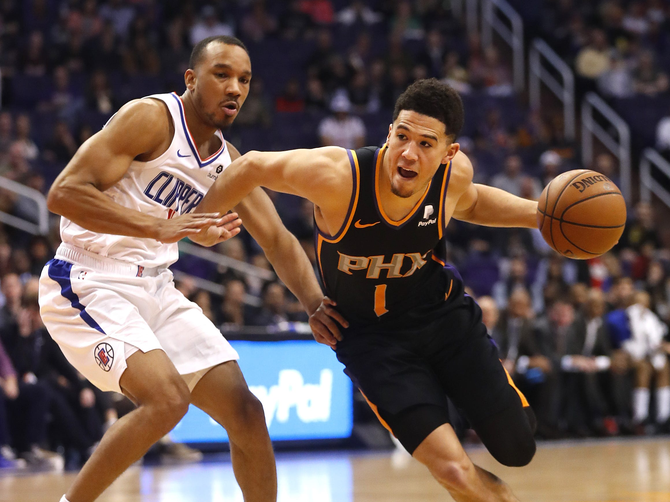 Suns' Devin Booker (1) drives the lane against Clippers' Avery Bradley (11) during the first half at Talking Stick Resort Arena in Phoenix, Ariz. on January 4, 2019.