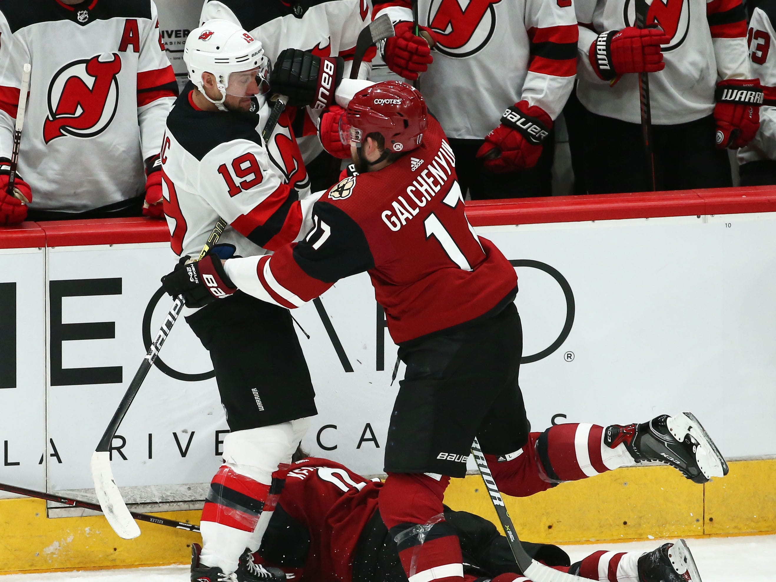 Arizona Coyotes' Alex Galchenyuk (17) comes to help Clayton Keller after he was driven into the boards by New Jersey Devils' Travis Zajac (19) in the 1st period on Jan. 4 at Gila River Arena.