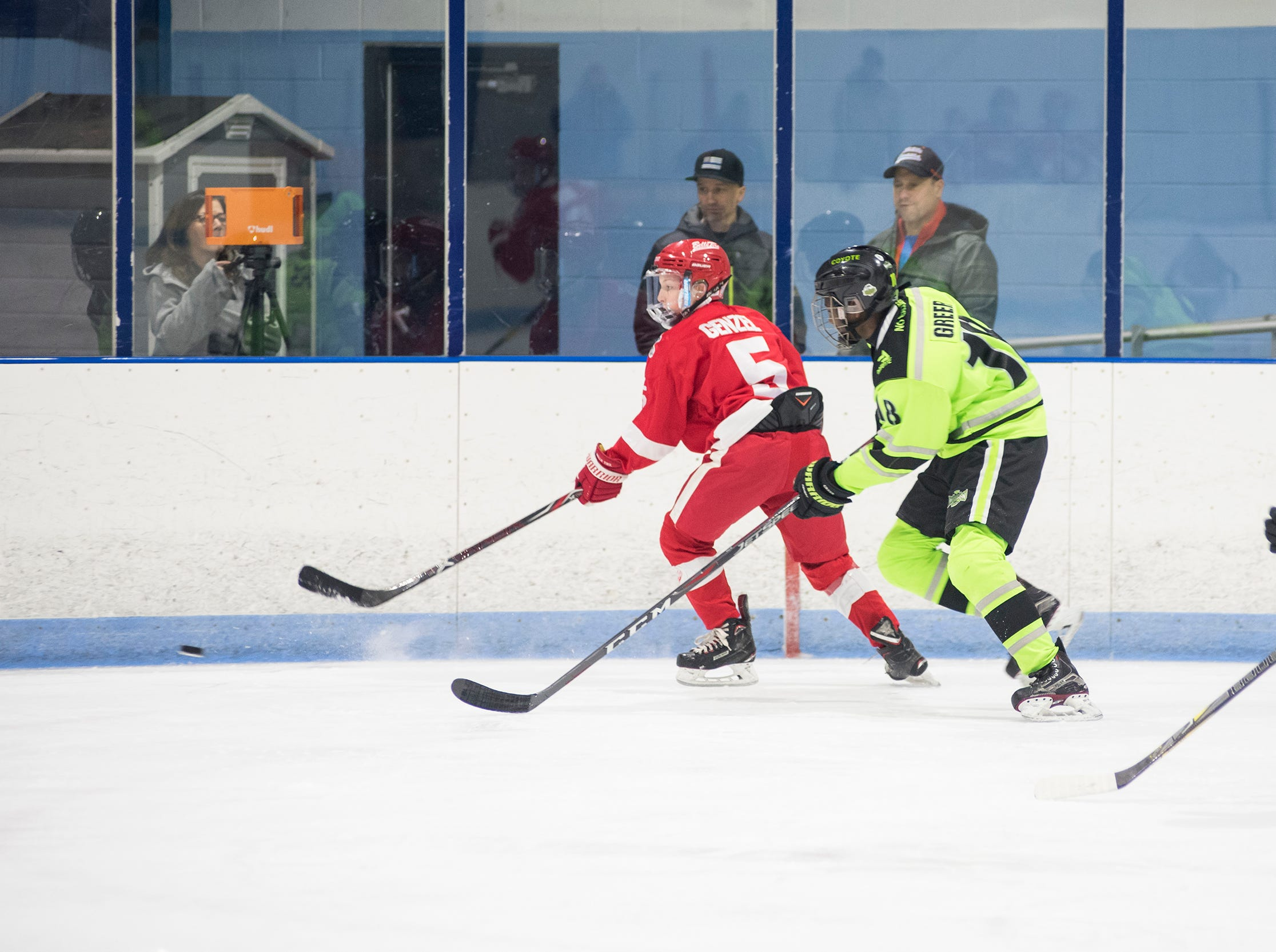 Chicago Mission forward John Greer (18) and Detroit Belle Tire defenseman Justin Genzel chase the puck during their PAAA-B Silver Stick Finals match Saturday, Jan. 5, 2019 at Glacier Pointe Ice Complex.