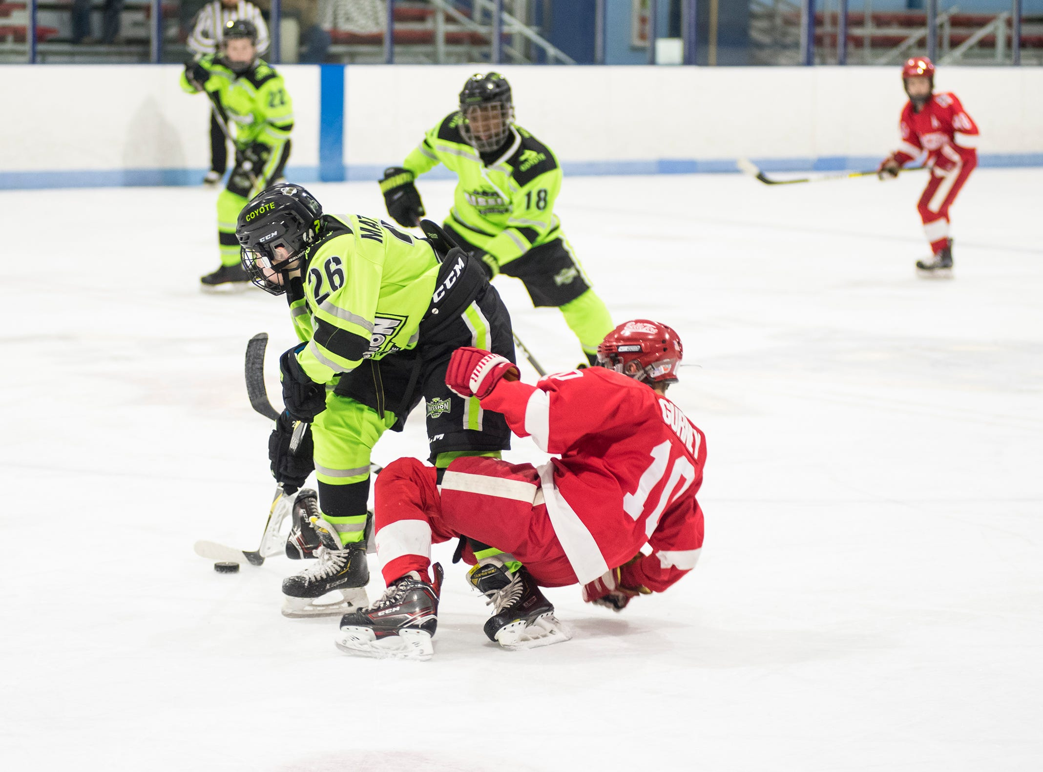 Detroit Belle Tire forward Fisher Gurney (10) falls to the ice trying to get the puck from Chicago Mission defenseman Luke Matthews during their PAAA-B Silver Stick Finals match Saturday, Jan. 5, 2019 at Glacier Pointe Ice Complex.
