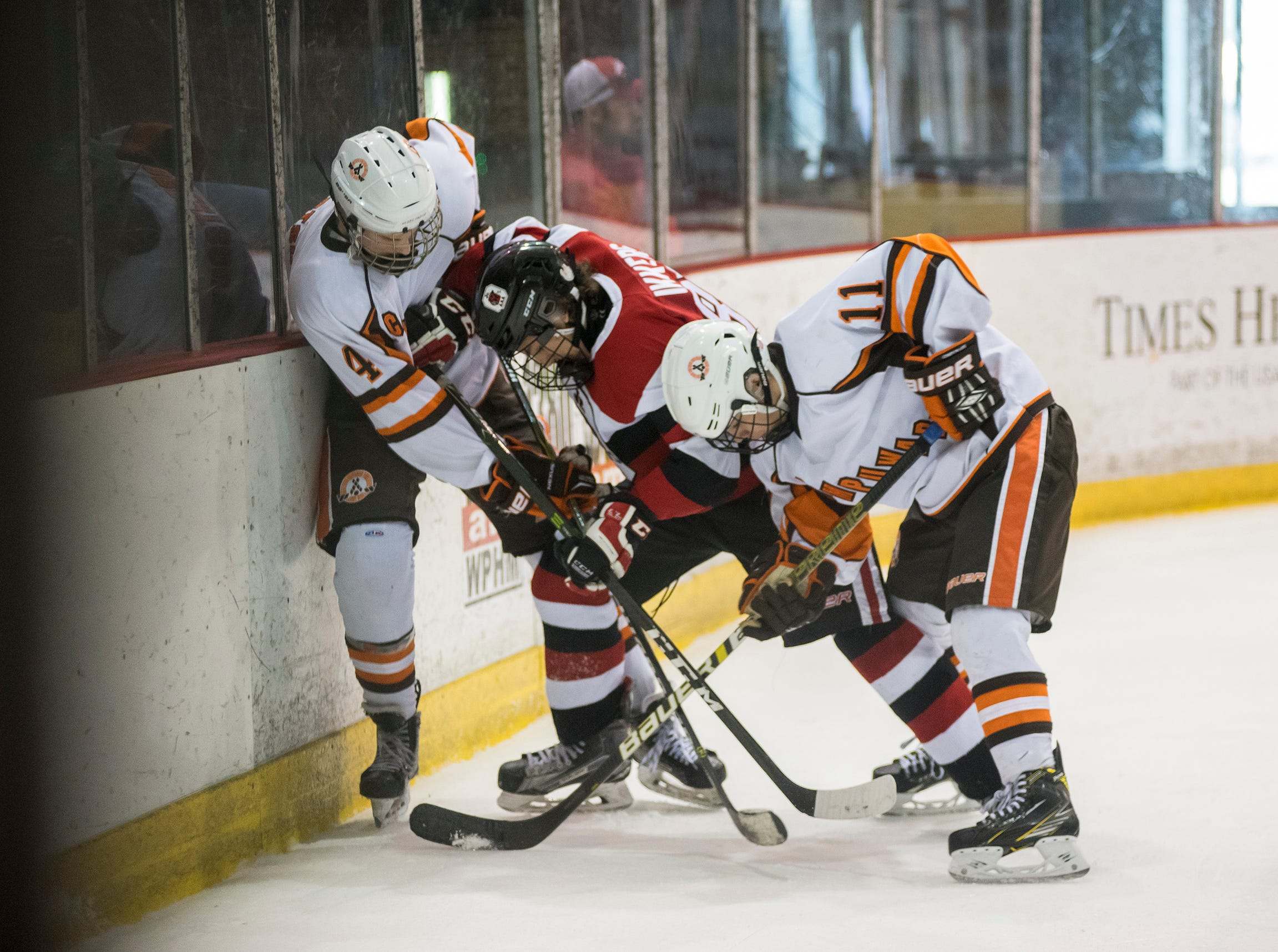 Detroit Compuware defenseman Brian Robertson (4), forward Brent Litchard (11) and Ottawa Jr. 67s defenseman Ryan Ikkers fight for the puck during their BAAA-B Silver Stick Finals match Saturday, Jan. 5, 2019 at McMorran Arena.