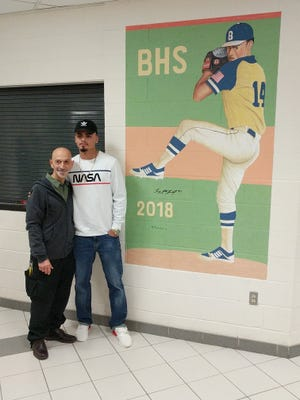 Lenny Torres and Rafael Figueroa stand in front of the new mural of Torres at Beacon High School on Friday.