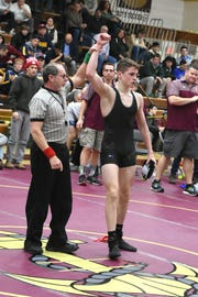 Dennis Robin has his hand raised after winning the 126-pound bracket at the Mid-Hudson Tournament.