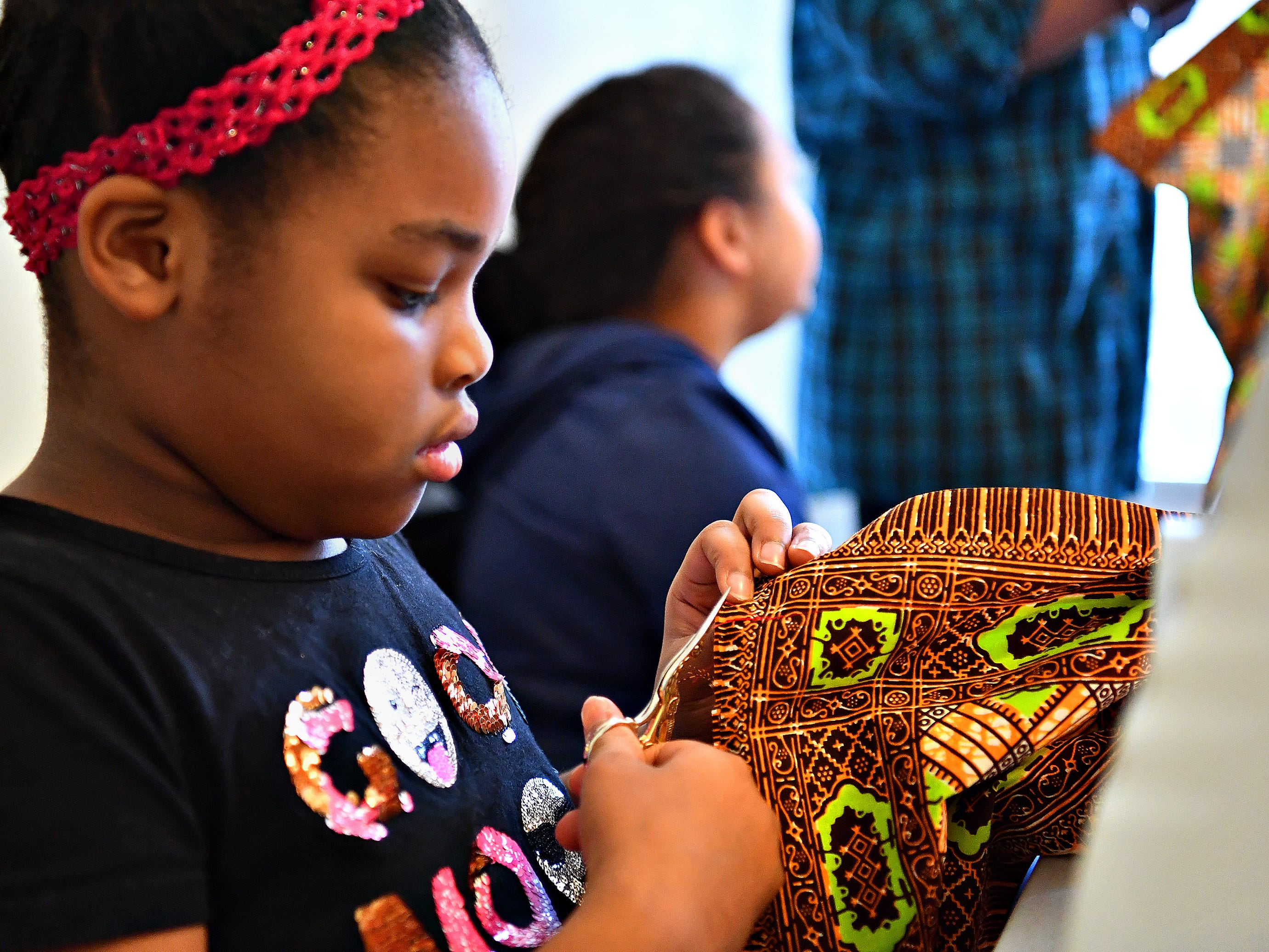 Maliah Shabazz, 8, of West York Borough, works on her pillow project during a sewing workshop led by Victoria Kageni-Woodard at her store, Gusa by Victoria, in York City, Saturday, Jan. 5, 2019. Dawn J. Sagert photo