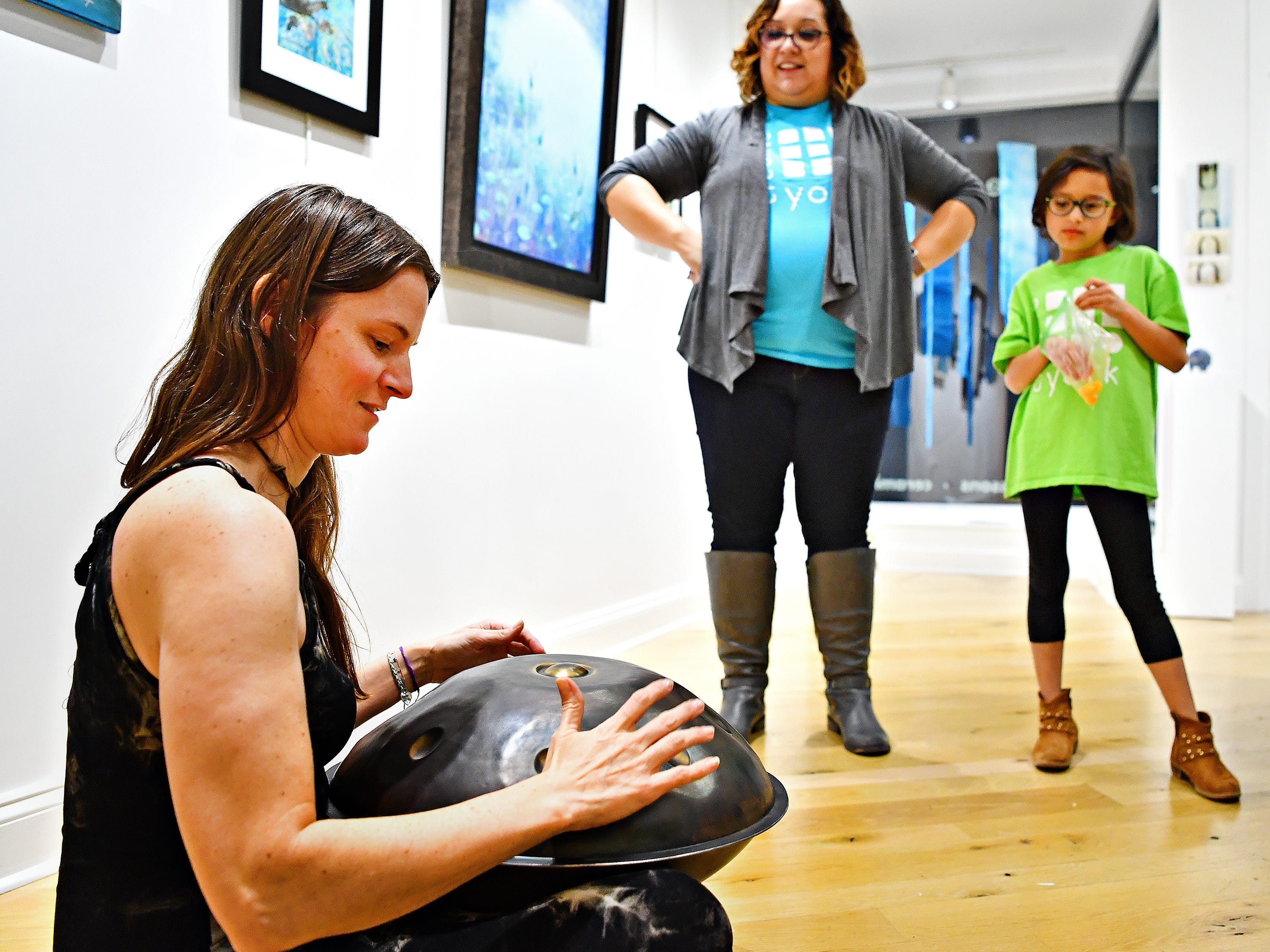 From right, Madelyn Smeltzer, 7, and her mother Samm Smeltzer, both of Manchester, look on as Chelsea Caroline, of Harrisburg, plays the handpan during the first First Friday of the year at Creative York in York City, Friday, Jan. 4, 2019. Caroline is one of the artists who's work is featured as part of the Water ER,  a multi-media, traveling art exhibit that focuses on the Susquehanna River, and is currently on exhibit in The Project Space at Creative York. For more information about the exhibit go to https://www.earthenwater.com/water-er/. Dawn J. Sagert photo