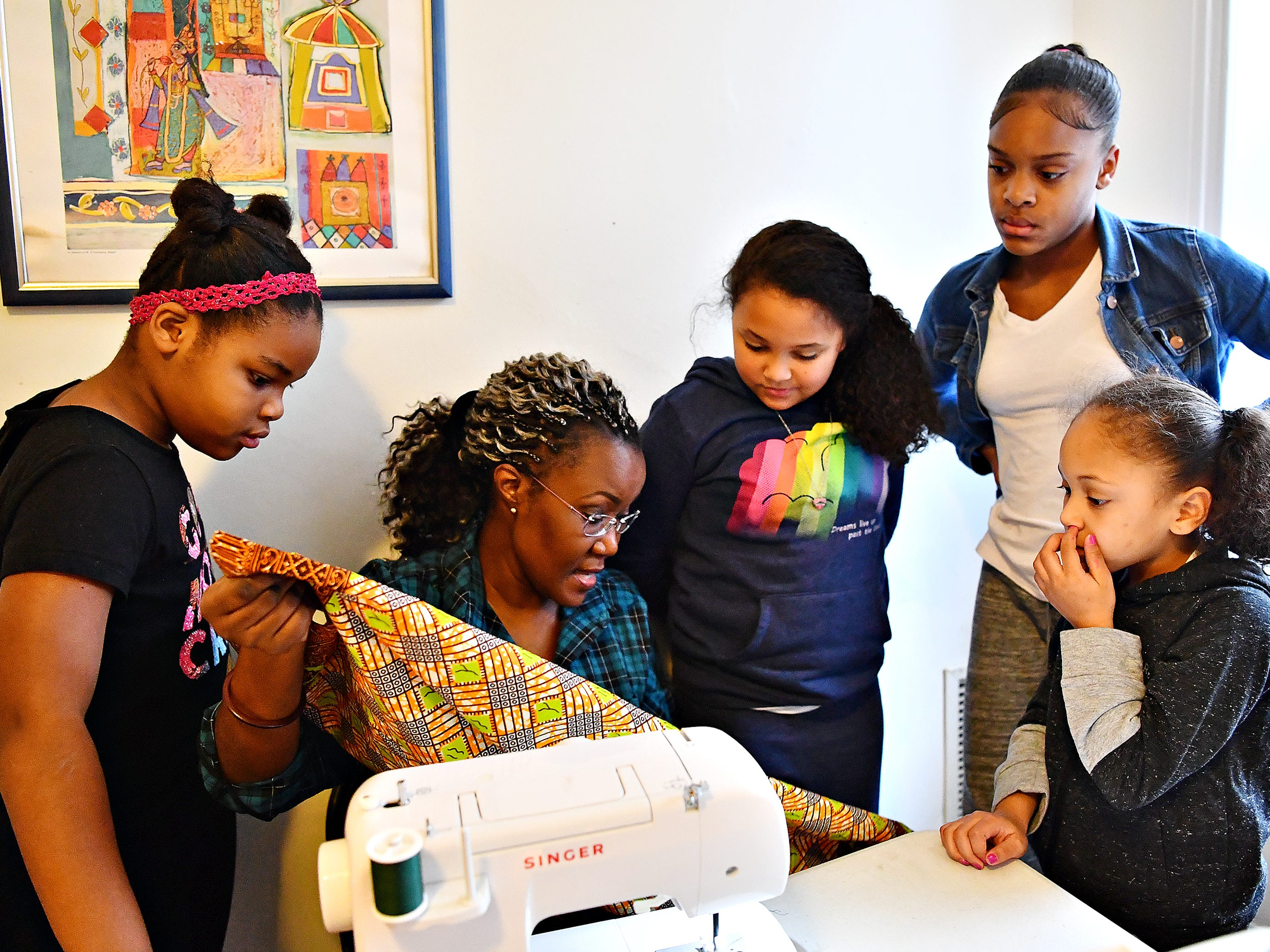 From left, Maliah Shabazz, 8, of West York borough, Victoria Kageni-Woodard, Ariana Kraft, 9, Mikya Holley, 11, and Jalaya Williams, 6, all of York City, discuss stitching the seams of a pillow while Kageni-Woodard leads a sewing workshop at her store, Gusa by Victoria, in York City, Saturday, Jan. 5, 2019. Dawn J. Sagert photo