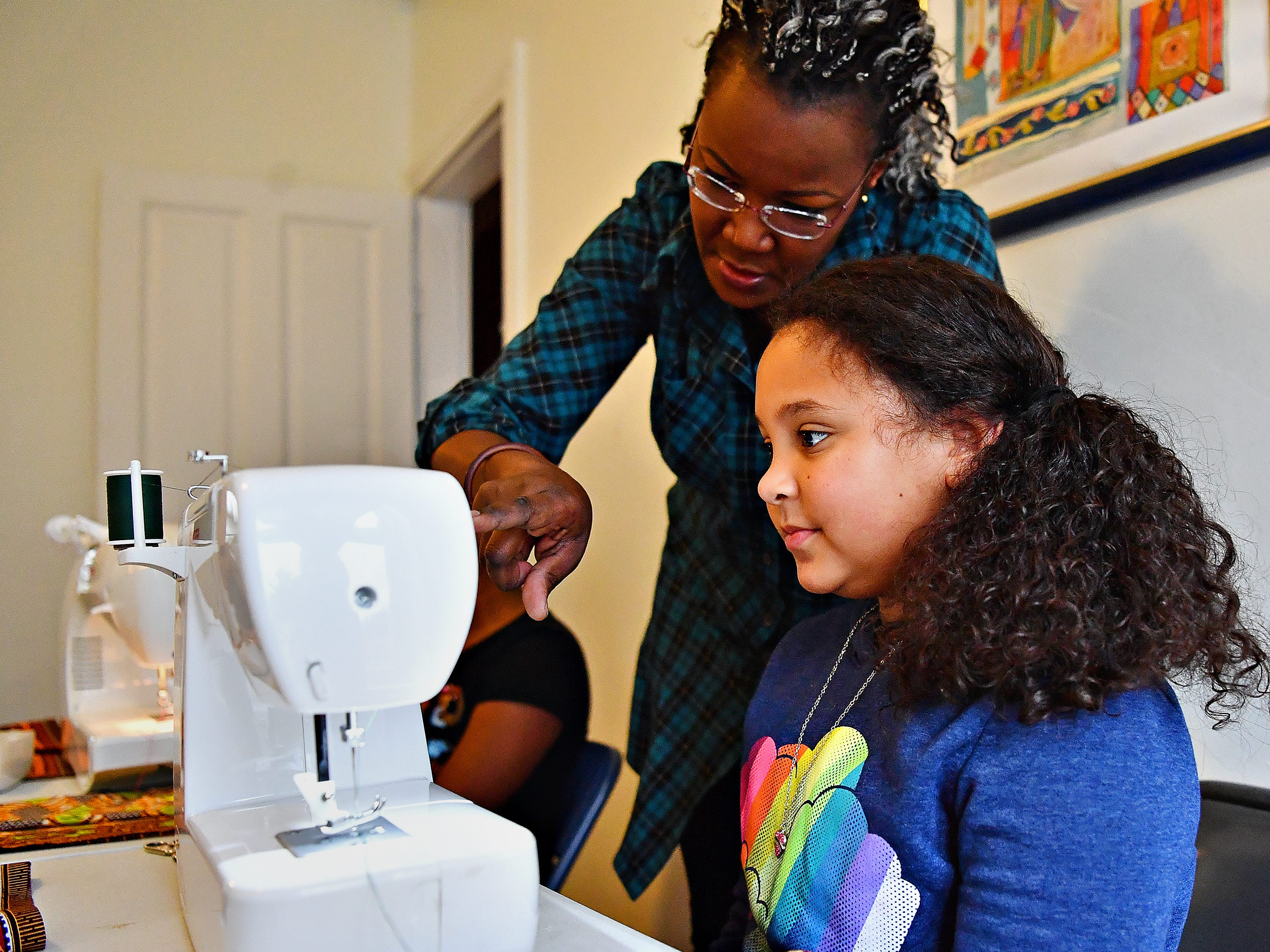 Victoria Kageni-Woodard, left, of Gusa by Victoria, works with Ariana Kraft, 9, of York City, as she leads a sewing workshop at her store in York City, Saturday, Jan. 5, 2019. Kraft would turn 10 the next day. Dawn J. Sagert photo