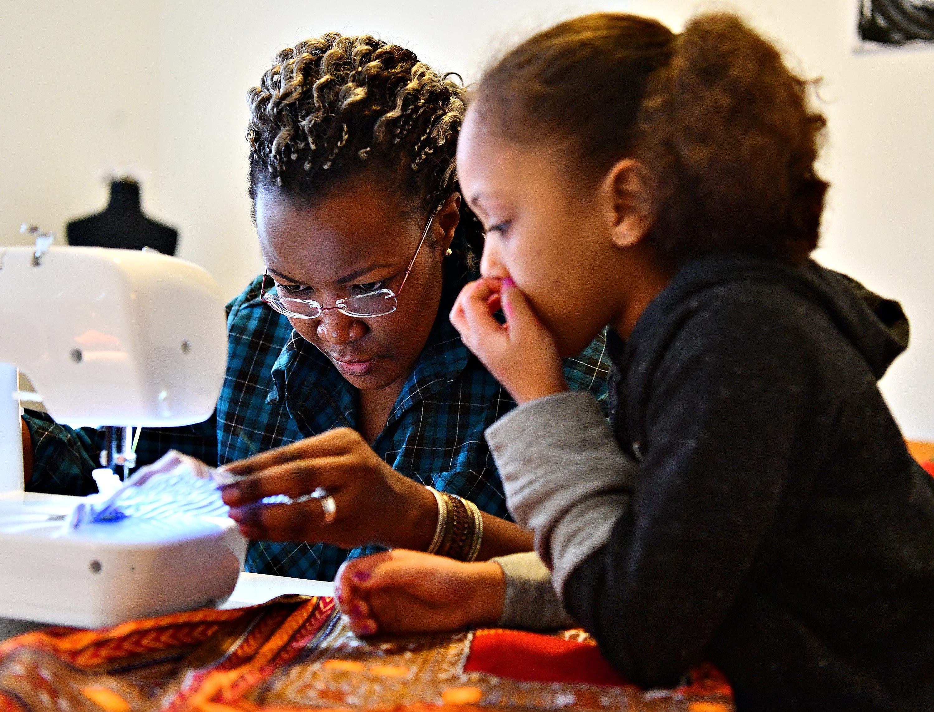 Victoria Kageni-Woodard, left, of Gusa by Victoria, works with Jalaya Williams, 6, of York City, as she leads a sewing workshop at her store in York City, Saturday, Jan. 5, 2019. Dawn J. Sagert photo