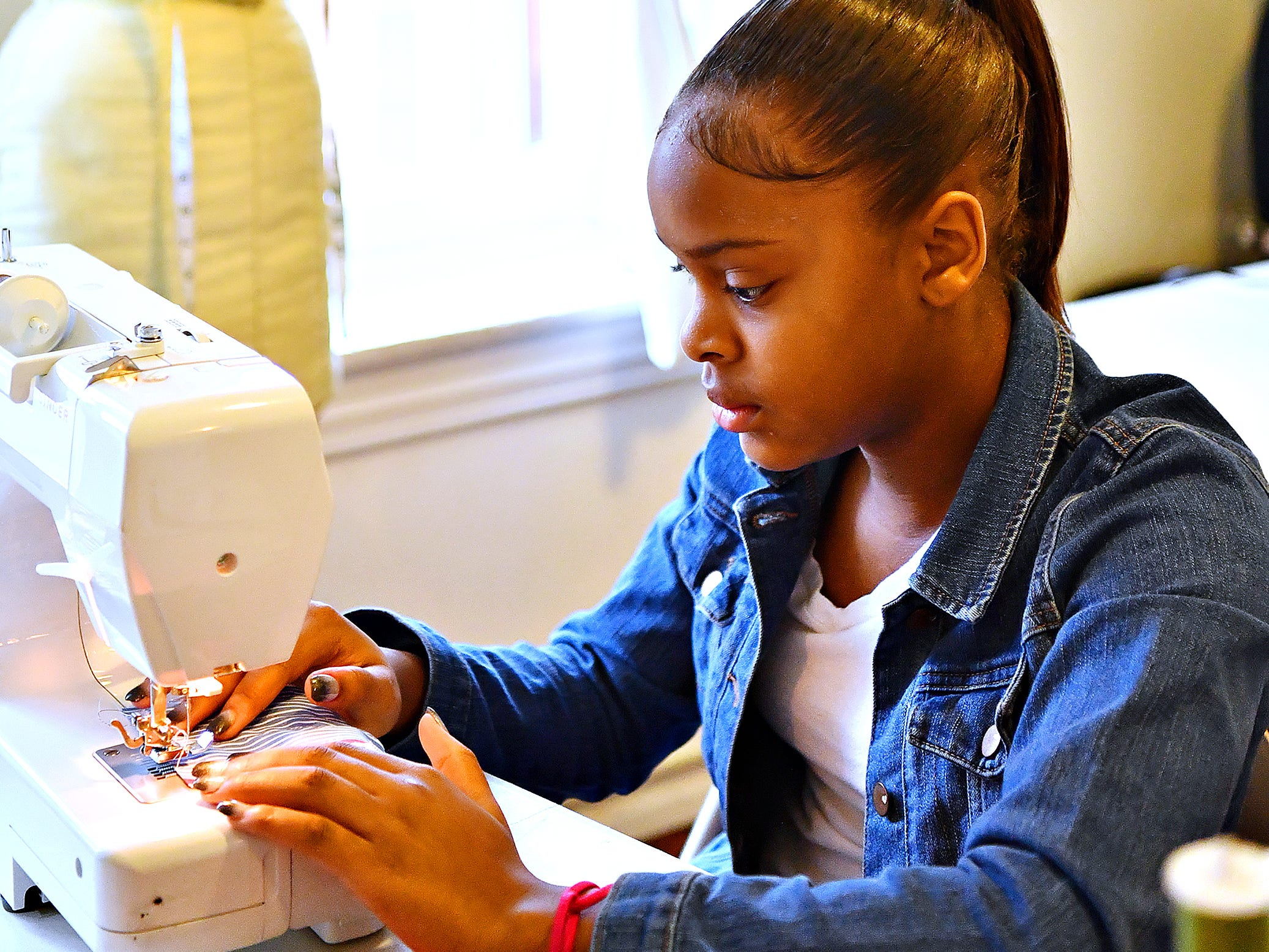 Mikya Holley, 11, of York City, practices sewing during a workshop led by Victoria Kageni-Woodard at her store, Gusa by Victoria, in York City, Saturday, Jan. 5, 2019. Dawn J. Sagert photo