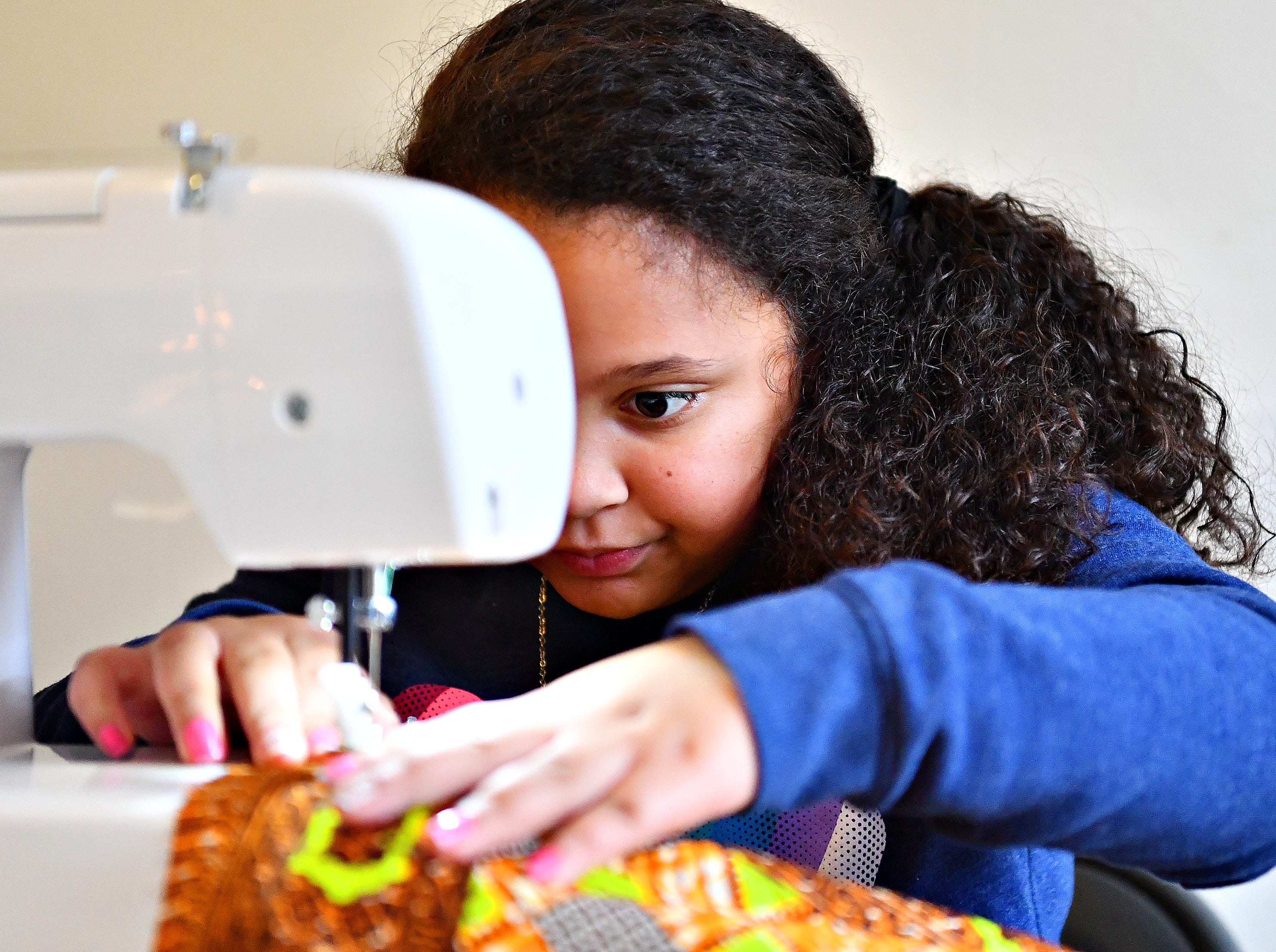 Ariana Kraft, 9, of York City, works on her pillow project during a sewing workshop led by Victoria Kageni-Woodard at her store, Gusa by Victoria, in York City, Saturday, Jan. 5, 2019. Kraft would turn 10 the next day. Dawn J. Sagert photo