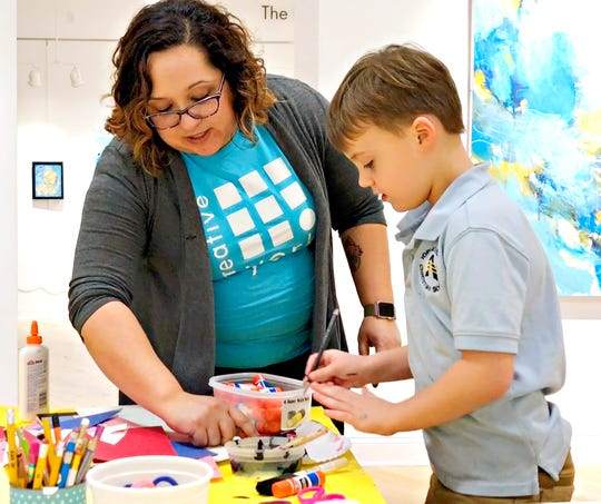 Creative York Board Member Samm Smeltzer, left, works with Josh Yordy, 6, of West York Borough, as he finishes making his paper penguin during the first First Friday of the year at Creative York in York City, Friday, Jan. 4, 2019. Dawn J. Sagert photo