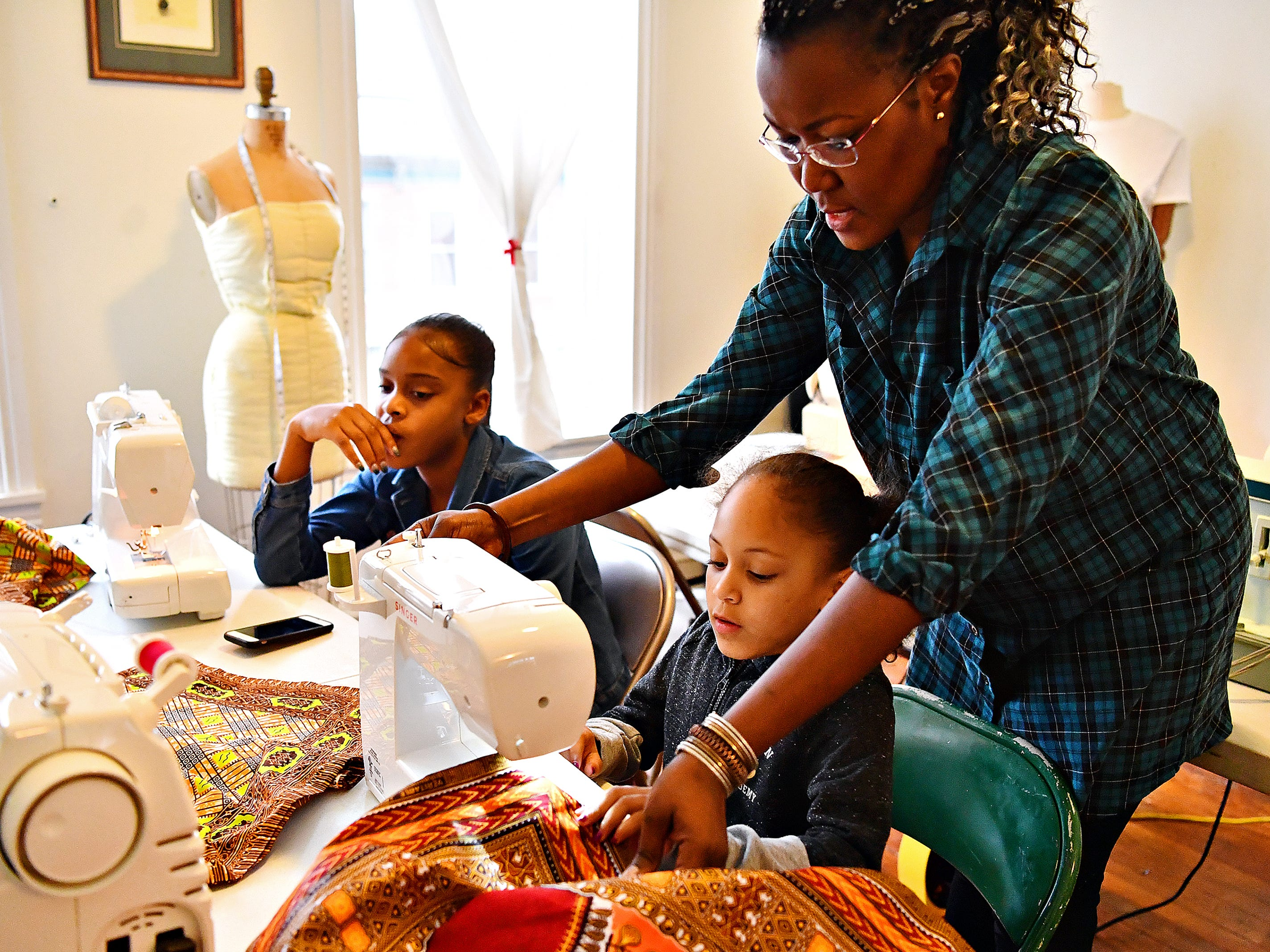 From right, Victoria Kageni-Woodard, of Gusa by Victoria, oversees a sewing project being worked on by Jalaya Williams, 6, while her sister Mikya Holley, 11, both of York City, looks on during a sewing workshop at her store in York City, Saturday, Jan. 5, 2019. Dawn J. Sagert photo