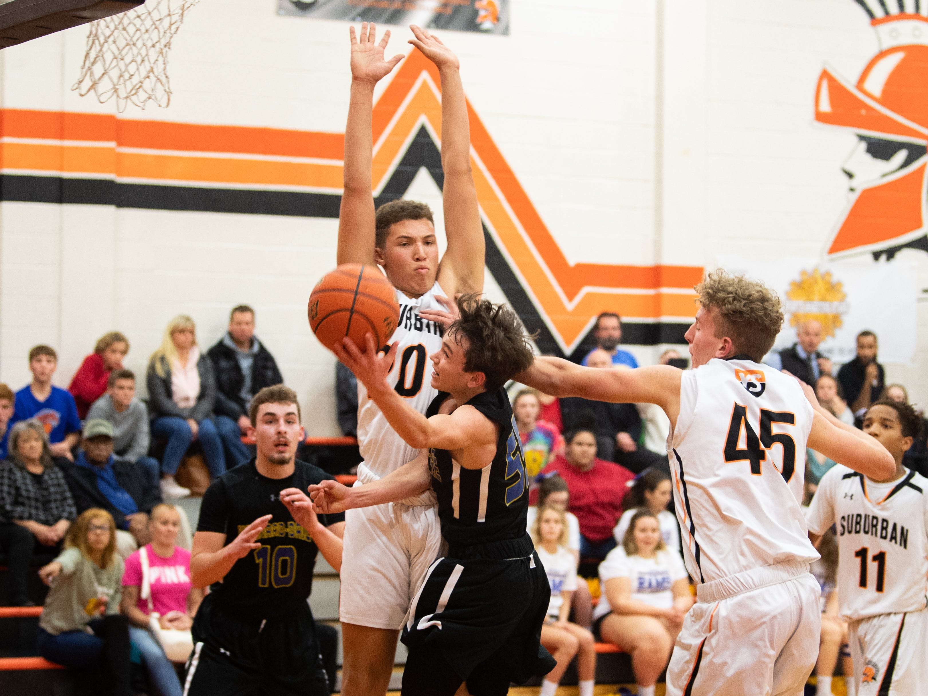 Aidan Hughley (20) and Alex Fuhrman (45) of York Suburban look to block Carter Day (55) of Kennard-Dale during the boys' basketball game, January, 4, 2019. The Rams beat the Trojans 65 to 63 in overtime.