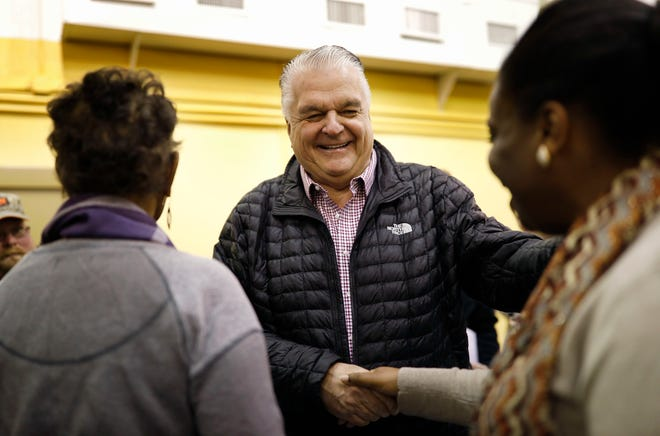 Nevada Governor-elect Steve Sisolak, center, shakes hands with Laniesha Dawson, right, at an International Alliance of Theatrical Stage Employees union hall Friday, Jan. 4, 2019, in Las Vegas. The visit was one stop on a road trip through Nevada before his inauguration Monday in Carson City, Nev. (AP Photo/John Locher)