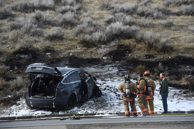 Reno Police and Reno Fire departments investigate a car crash and fire at the intersection of West Fourth Street and North McCarran Boulevard in west Reno on Jan. 5, 2019.